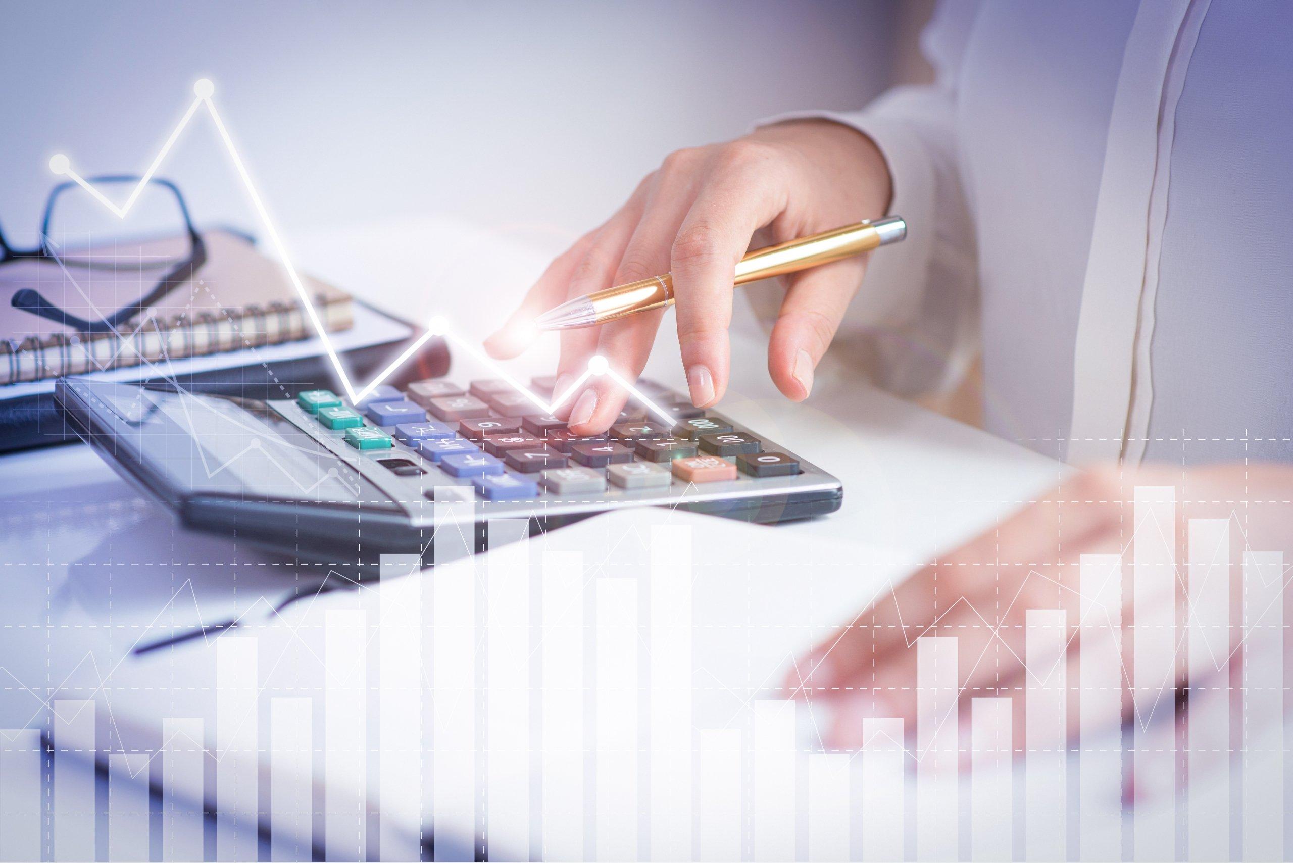 Imagen de una persona haciendo cuentas con una calculadora y papeles