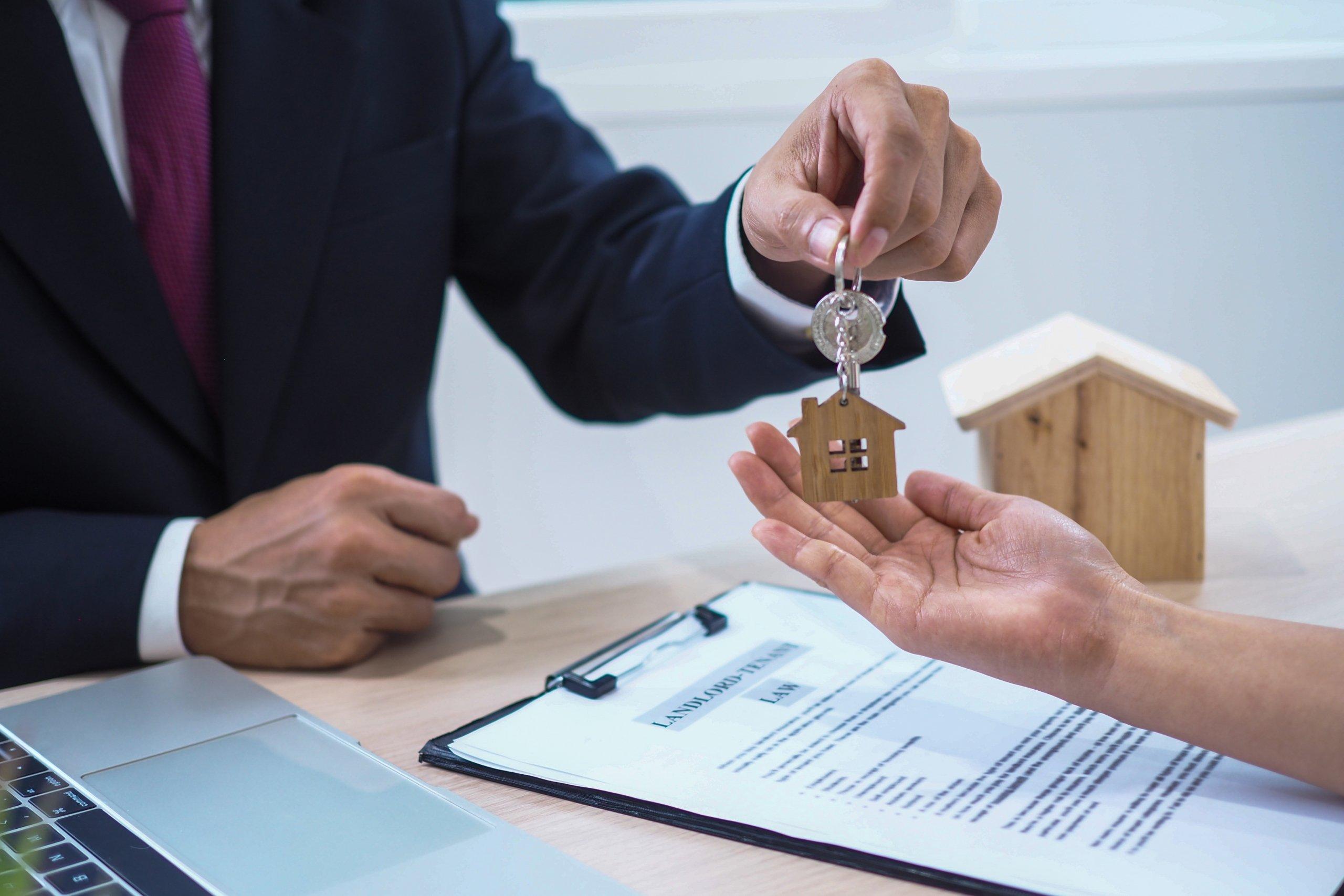 Agente inmobiliario haciendo entrega de las llaves de un inmueble a una persona