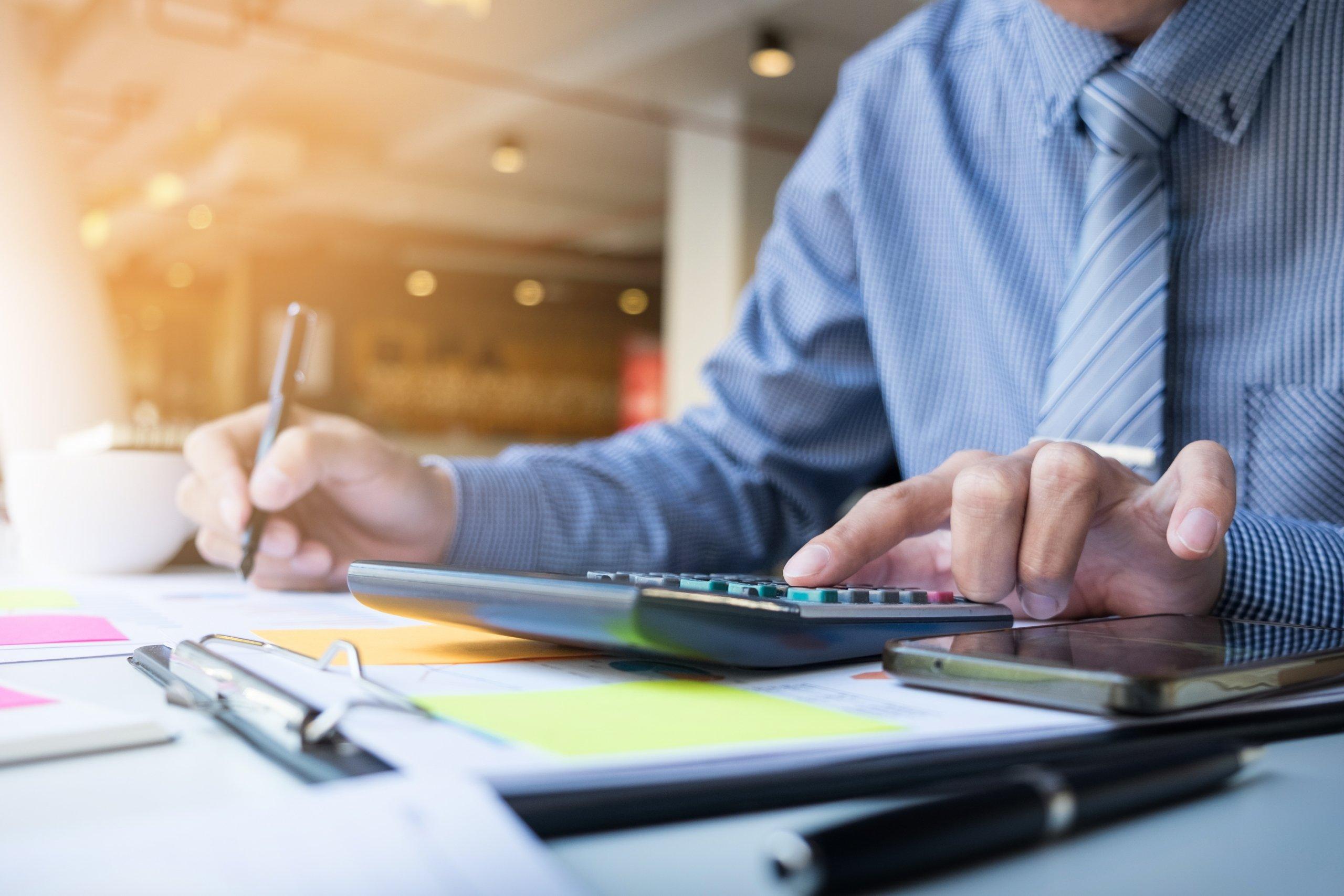 Persona haciendo cuentas con calculadora para el informe de evaluación