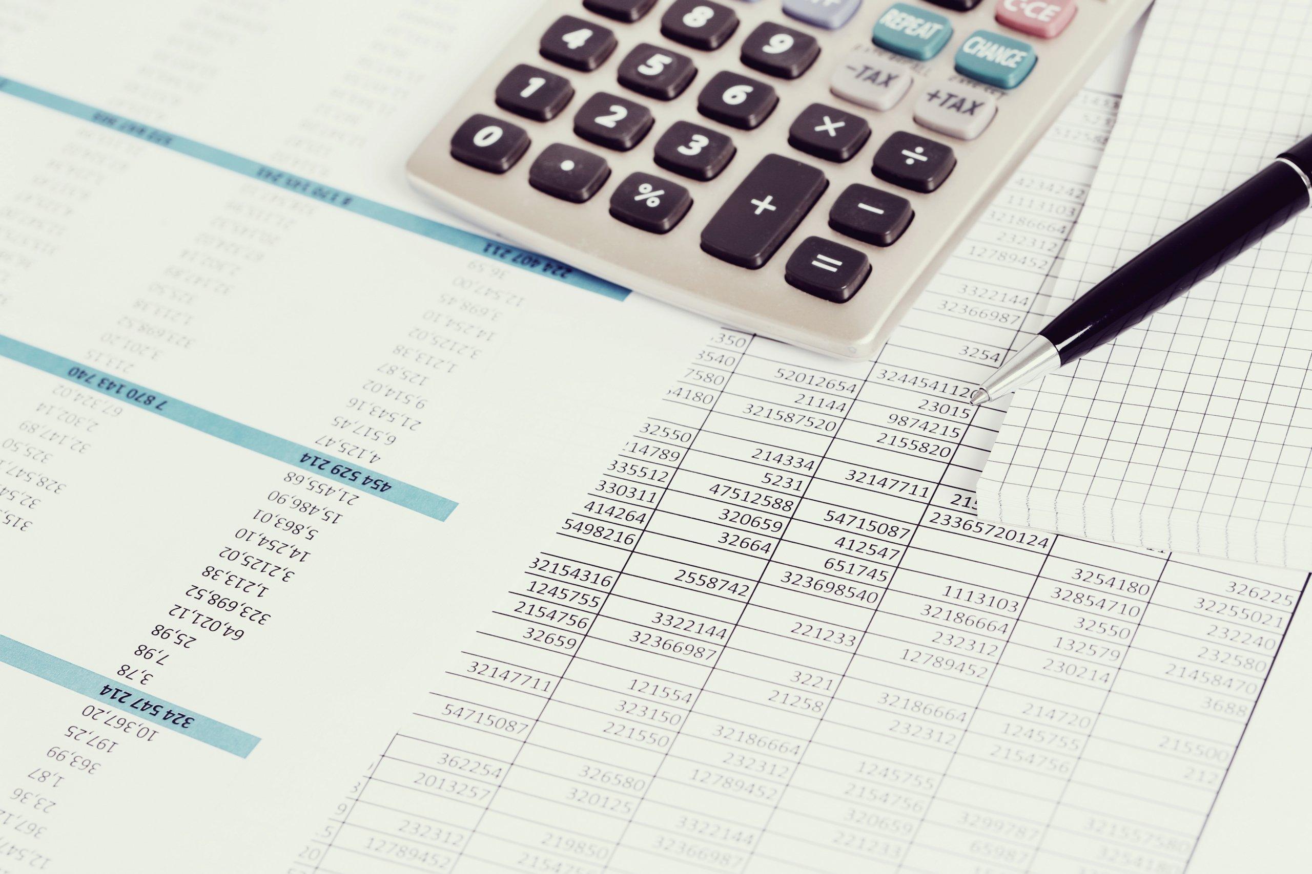 Persona calculando los tributos locales con calculadora e informes